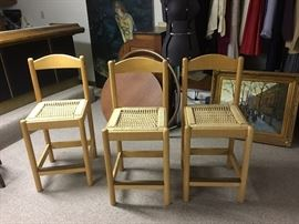 Three light wood and rope counter chairs.