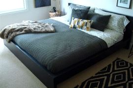 King bed frame with pair twin mattresses and bedding.