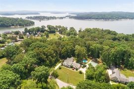 2.14 Private Acres, approximately 5,000 square feet. Virtually 2 houses in one; two full kitchens, 5  or 6 bedroom, 5 full bath, boat dock on lake Chickamauga, power pole for camper on lake at dock, detached four bay garage with hydraulic car lift, pool.
