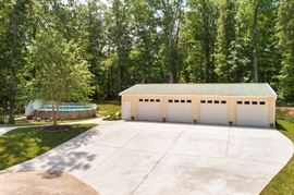 Newly constructed detached four bay garage with hydraulic car lift and restroom