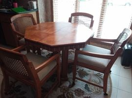 Octagon Dining room table with 4 cane back chairs on casters, newly upholstered!