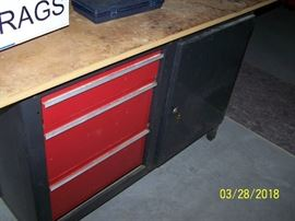 Metal cabinet with drawers, locking door and fiberboard top.