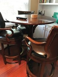Two matching pub style tables in cherry with leather and nail head barstools