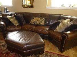 BROWN CURVED LEATHER SECTIONAL WITH OTTOMAN