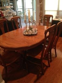 This extra large oval dining table has 6 chairs,  4 leaves, and pads. (There is a storage area under the table for the leaves- great feature.)