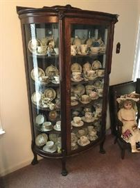 Antique Oak Bow Front Chain Cabinet , large collection of vinta , antique doll and chairge cups and saucers