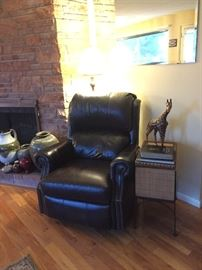 Leather Rocker Recliner, Floor Lamp, Wicker Storage Chest Stand, Bible, Leaves of Gold Poems, Giraffe Statue.