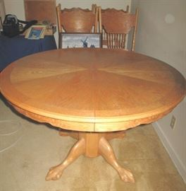 Round oak claw foot table and pressed back chairs.