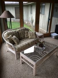 Rattan loveseat and glass-top coffee table.