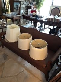 Low leather (I believe) wood antique sofa and lampshades.  Gateleg table and crystal, Small pedastle side table.  (Painting, dining room tables and chairs and display cabinet sold)