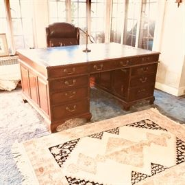 Vintage leather-topped partners desk, very good condition.  The leather could use some refurbishing (there are no tears, just a some dings, minor discoloration in spots -- normal wear & tear from use over the years) and re-gilding to the scrolls along the edges.