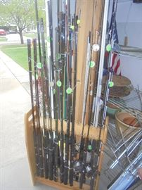 One side of a pool table  que rack full of poles