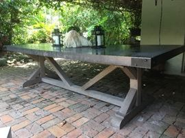 """Concrete Top on Teak Base Patio Table from Restoration Hardware (9-foot) - """"Our eclectic table pairs stout teak beams with an equally sturdy concrete top for a mix of materials that will age beautifully outdoors. Aluminum banding encircles the table's apron. Tabletop is handcrafted from concrete composite in a deep slate grey Aluminum banding has a black powdercoated finish Substantial teak table base provides enduring strength and features a weathered grey finish that will acquire a soft, aged patina over time Inherent variations in the shading and color of the concrete, as well as in the casting process, make the tables truly unique; no two are alike Concrete may exhibit spotting and hairline cracks due to exposure to the elements; scratches may appear due to usage Guides under the table top prevent the top from shifting Teak base withstands sun, rain, frost and snow.""""  $3,000    Link to Restoration Hardware site - https://www.restorationhardware.com/catalog/product/product.jsp?produ"""