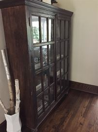 Side view of storage cabinet with glass front panel in doors