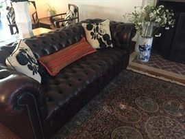 Chesterfield sofa, shown with amazing pillows and and a Chinese Silk area rug and vase with blossoms
