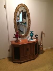 Cabinet record player with radio.  Oval mirror.