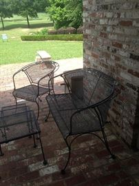 Black patio settee, chair, and stack tables