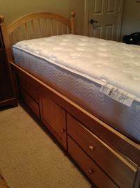 One of two twin beds with under-storage