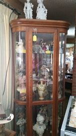 Figurines in curved glass curio cabinet