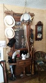Antique umbrella stand,  vintage hats, umbrellas,  walking sticks,  beaded hanging lamp, clock