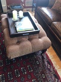 Custom made, tufted ottoman.  Beneath it, a handmade Bokara carpet.