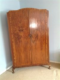 Antique wardrobe cabinet holds clothes, quilts.