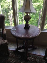 This is an elegant round table that is painted in the predominant colors of brown/maroon and gold. Notice its unusual and decorative base and feet.  The lamp is not included. Price for the table only: $200.
