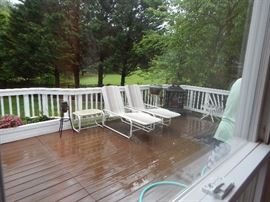 Back deck with two chaise lounges, fire place, grill and more.