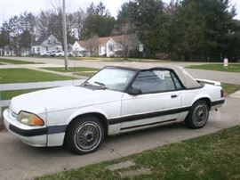 1988 Ford Mustang convertible, 183,835 miles, white, red interior, runs good, needs new top. Was $1400, marked down to $999, OBO.