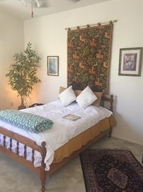 Great bedroom furniture, a silk rug, and a quilted Renaissance style wall hanging.