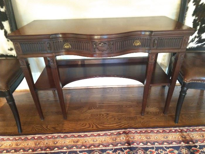 "Federal style mahogany console, having a modified serpentine top, above a frieze drawer decorated with alternating fluting and parterre centering a reserve of bas relief floral swags, the whole rising on four front square tapering legs with fluting, joined by a lower shelf, measuring 31""h x 48""w x 21.5""d."