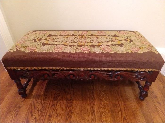 "Renaissance Revival upholstered bench, late 19th cent., of rectangular form, the seat upholstered in floral needlepoint on a chocolate ground, with brass nailhead trim, above block and turned legs joined by a pierced carved scrollwork front stretcher; measures 17""h x 39""l x 18""w."