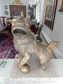 One of a pair of unusual Asian foo dogs, on a limestone base.