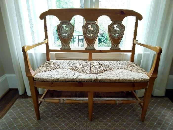 "French Provincial style carved pine bench, with shaed back and woven rush seat; measures 40"" h x 43.5""l x 18.5""d."