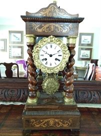 "Late 19th century rosewood Empire style portico clock, the crest and base marquetry inlaid and supported by four spiral twist columns with gilt bronze capitals; measures 17""h x 9""w x 5""d."