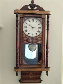 "19th century Continental marquetry inlaid regulator clock, with a carved leaf pediment above the clock face, flanked by turned pilasters, terminating in an inlaid scroll-link base; measures 38.5""h x 15""w x 5.5""d."