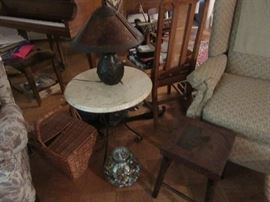 Marble top table with cast iron legs .    The carved table next to the marble table is carved on top and legs. The jar is filled with early marbles, and the Lamp is metal