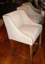 Three oversize upholstered bar stools.