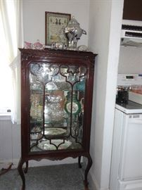 Antique glassware and platters in vintage china cabinet.