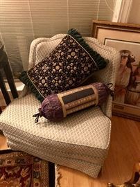 slipper chair in  a neutral fabric with two decorator pillows. There are over 30 throw pillows in the house