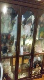 3 door curio cabinet with several dolls