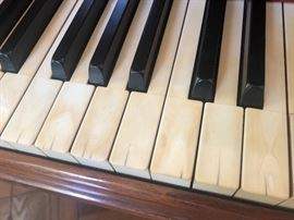 The original ivory keys have some discoloration and hairline cracks