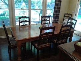 Large rustic dining table with eight chairs and two leaves