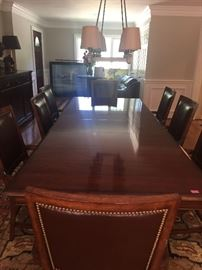 Pristine Dining room table with two leaves and 8 wood and leather arm chairs.