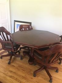 Game table with rolling swivel chairs with leather seats