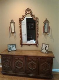 Ornate mirror with sconces.
