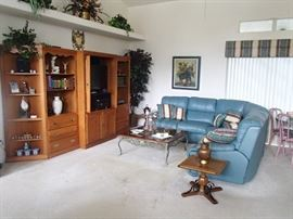 living room: teal sectional, wall unit