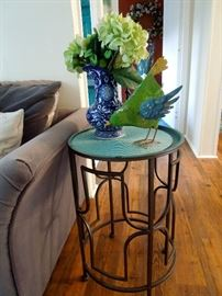 Metal side table. Painted metal bird sculpture and cobalt blue decorative vase with floral arrangment