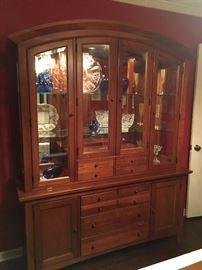 Beautiful lighted cherry china cabinet.