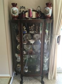 I love this early 1900's oak curved-glass china cabinet with claw feet filled with beautiful pieces/collectibles -- notice the wonderful matching vases!